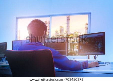 Professional technician sitting in control room monitoring process petrochemical plant, Asian broad man operate process plant, Engineers work