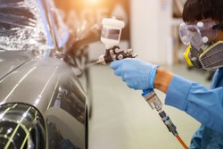 Professional technician Spraying the varnish to the car Ready to wear protective gear.The concept of care scratching paint.Car coating