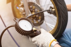 Professional technicians are inflating the tires of a motorcycle using a standard air pressure check device.
