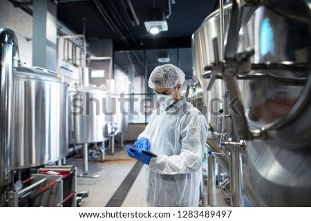Professional technologist using tablet in production plant checking productivity and quality.