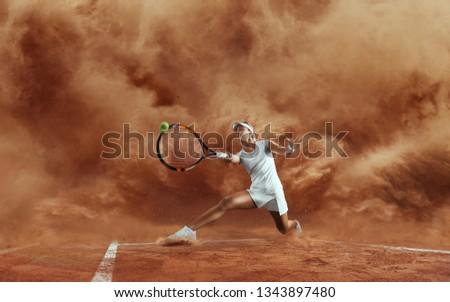 Professional tennis player. Female tennis player in action during game on sand background.