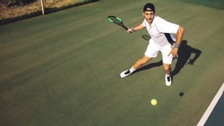 Professional tennis player hitting a forehand while playing on a hard court. Young man in sportswear practicing tennis on a hard court.