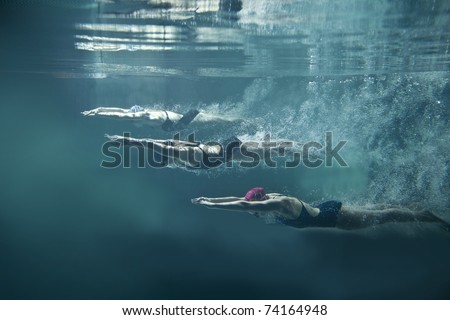 Professional three swimmers under water isolated