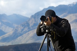 Professional travel nature cameraman/photographer (male) photographing and video nature and landscape outdoor. Real people. Copy space