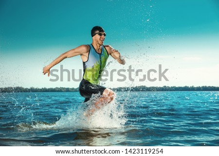 Professional triathlete swimming in river's open water. Man wearing swim equipment practicing triathlon on the beach in summer's day. Concept of healthy lifestyle, sport, action, motion and movement. Foto stock ©