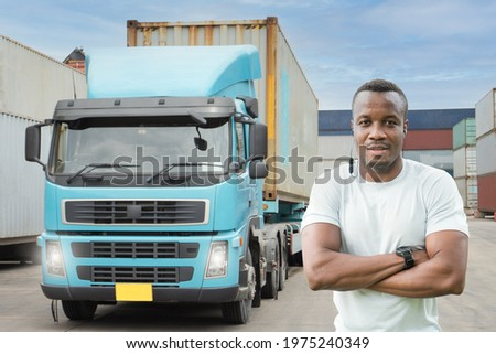 Professional truck driver Standing arm folded smiling in front of the semi truck container yard. African young man cheerful proud business owner  Delivery transportation carry Import Export Warehouse