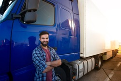 Professional truck driver with crossed arms standing by his semi truck. Trucker occupation and transportation services.