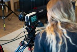Professional video camera black magic 4k during set with female operator