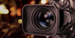 Professional video camera on dark bokeh background