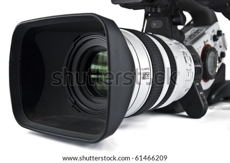 Professional video camera pointing to camera left. Lens hood and front of lens are in focus, the rest is soft