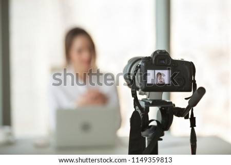 Professional video camera recording successful businesswoman giving online training or filming business course