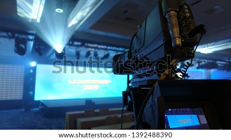 Professional video camera with long lens set up to shoot a corporate event, fog creates dramatic lighting effects                                #1392488390