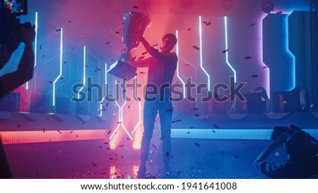 Professional Video Games Player Tournament Winner Celebrates Victory Cheering and Holding Trophy. Big Stylish Neon Bright Championship Arena doing Pro Computer Gaming Event with Online Streaming Photo stock ©