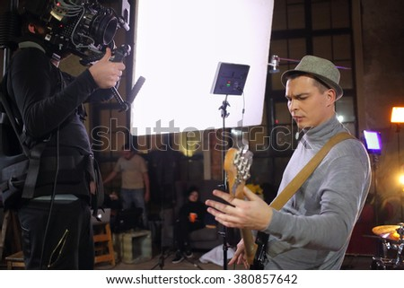 Professional video shooting a musician playing the guitar in the studio Сток-фото ©