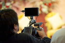 Professional videographer Filming a video at the event with a camcorder and recording with professional tools to get complete footage and satisfy customers well