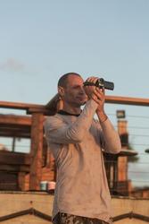 Professional videographer holding a camera. Focus on camera. Man hand holds digital black video camera