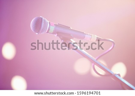 Professional vocal microphone on stage in music hall.Retro style mic on stand in close up.Pink vibrant lights on scene.Sing a song using pro audio equipment