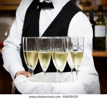 professional waiter in uniform is serving wine