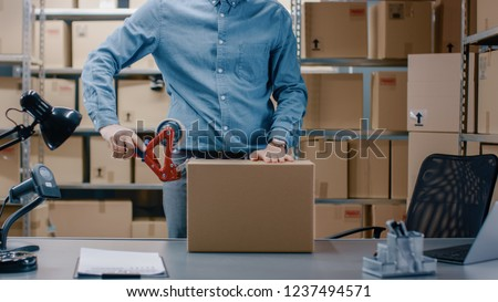 Professional Warehouse Worker Checks and Seales Cardboard Box Ready for Shipment. In the Background Person Working in the Rows of Shelves with Cardboard Boxes with Ready Orders.