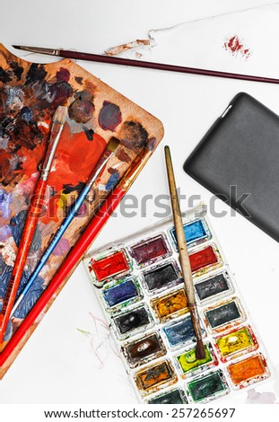 Professional watercolor paint and brush, cell phone on paper background with spots. Concept art background.