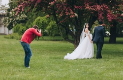 Professional wedding photographer in the process of photographing with the newlyweds in nature. Photography, concept.
