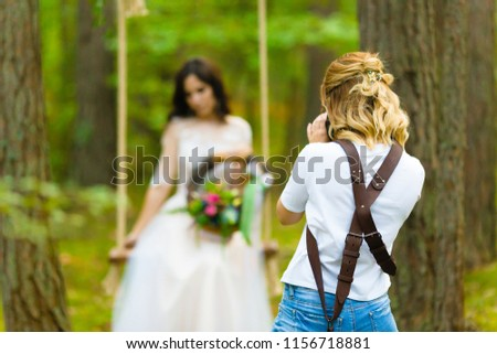 Stock Photo Professional wedding photographer taking close-up portraits of the bride on a rope swing with rustic style bridal bouquet
