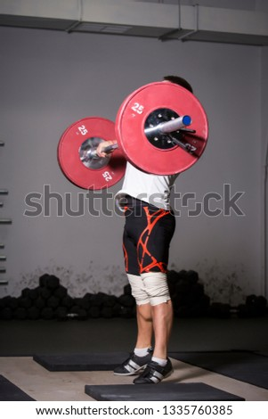 Professional weightlifter in knee wraps performs an exercise Snatch with the weights of 70 kilograms on the weightlifting platform with the barbell bars and dumbbells on the background.