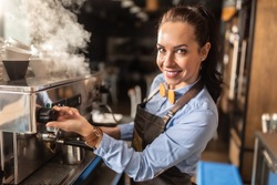 Professional, well-dressed female barista steams off coffee machine in a cafe.