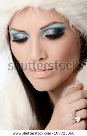Professional winter makeup and fur hat on beautiful woman.