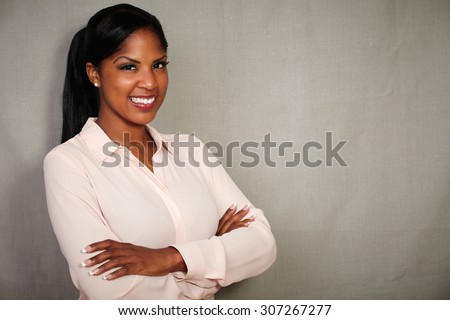 Professional woman in button down shirt smiling with arms crossed - copy space