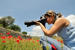 professional woman photographer in a field with poppies in spring