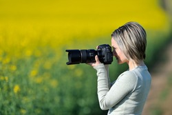 professional woman photographer on field in summer