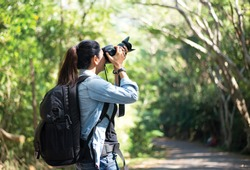 Professional woman photographer taking camera outdoor portraits with prime lens in the photography nature. Greenery tone 2017.  Travel and Lifestyle Concept