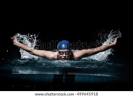 Professional woman swimmer swim using breaststroke technique on the dark background