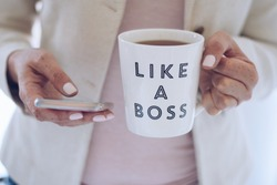 Professional woman using mobile phone and holding a cup that says LIKE A BOSS