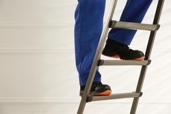 Professional worker climbing up ladder indoors, closeup view