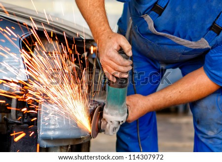 professional worker in automotive industry grinding metal on a body car