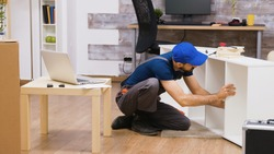 Professional worker in overalls consults furniture assembly instructions from laptop. Worker wearing a cap.