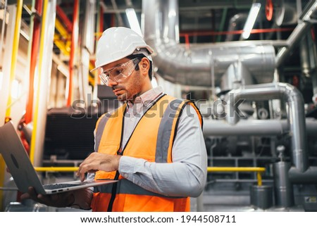 Professional worker of modern factory using laptop controlling program to automatic machinery. Engineering with laptop Programmable Logic Controller to manage large machine working full automatic. Сток-фото ©