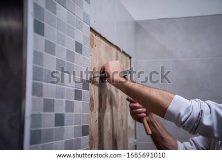 professional worker remove demolish old tiles in a bathroom with hammer and chisel