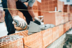 Professional worker using pan knife for building brick walls with cement and mortar