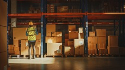 Professional Worker Walking with a Cardboard Box Places it on a Shelf with other Goods in Retail Warehouse. Product Delivery Distribution Logistics Center. Side View Shot