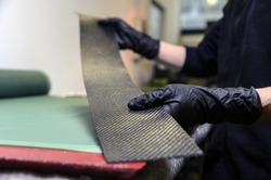 Professional worker with gloves manually realizes a component in real carbon fiber. Measurement, cutting and preparation of different types of carbon fiber: plain, twill and satin.