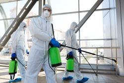 Professional workers in hazmat suits disinfecting indoor accommodation, pandemic health risk, coronavirus