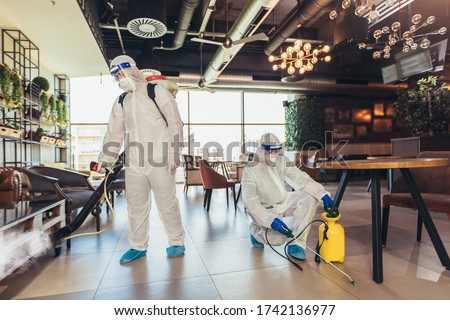 Professional workers in hazmat suits disinfecting indoor of cafe or restaurant, pandemic health risk, coronavirus
