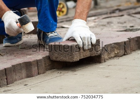 professional  Workers  Laying Paving Slabs by mosaic close-up in blue overalls