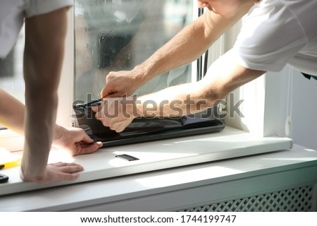 Professional workers tinting window with foil indoors, closeup