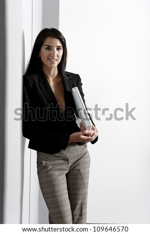 Professional working woman in corporate business suit holding a laptop computer