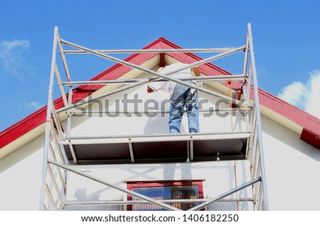 Professional workman is painting exterior walls and wooden window frames of ancient house at scaffold tower, outside home renovation in close up under sunny blue sky