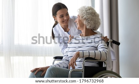 Professional young female medical worker in white uniform communicating supporting smiling older mature disabled woman in wheelchair indoors, retirement house healthcare rehabilitation concept.
